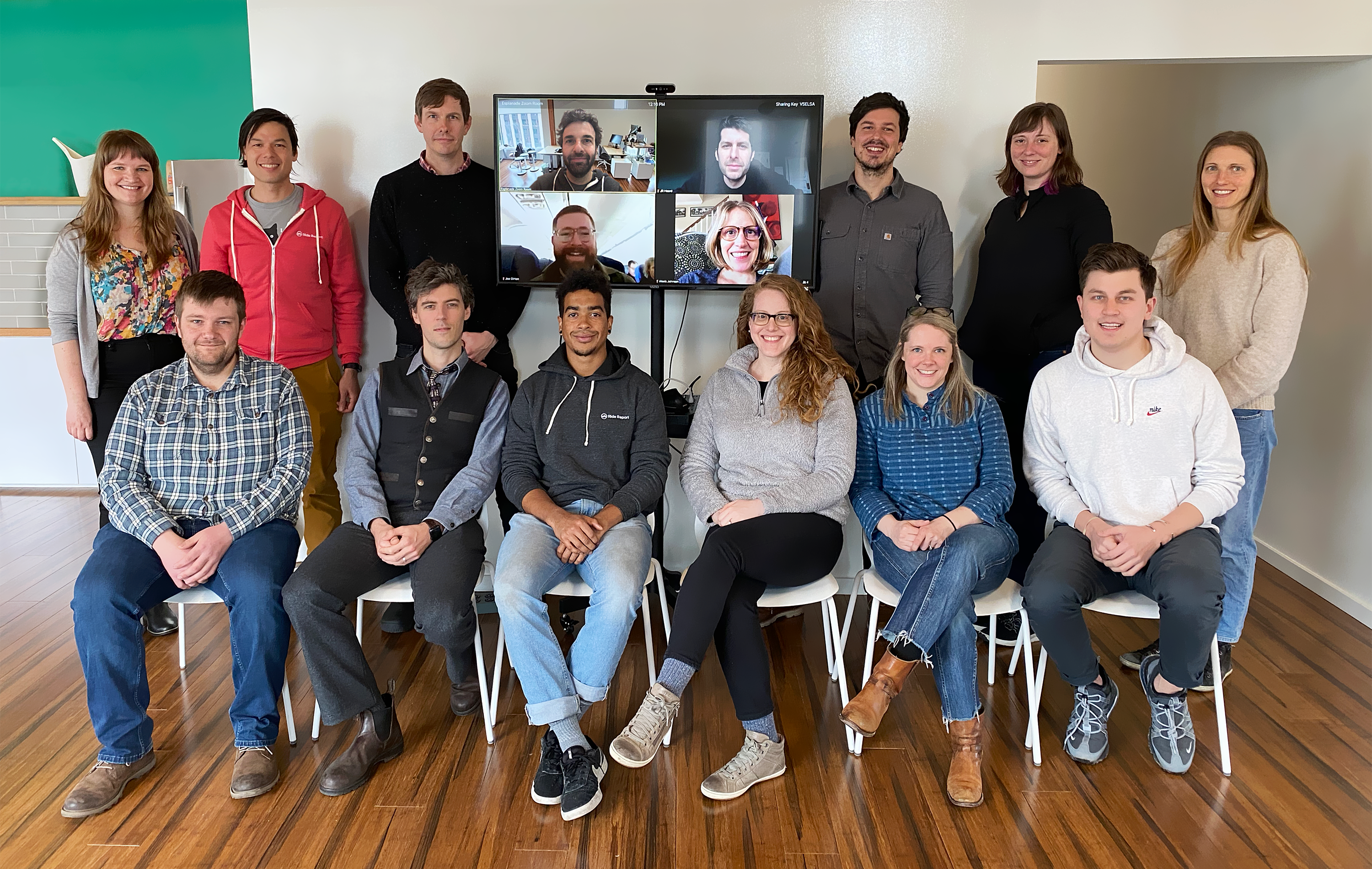 12 people in 2 rows, the first row sitting on chairs, the second row standing around a flat television screen where 4 people are pictured who have video conferenced in