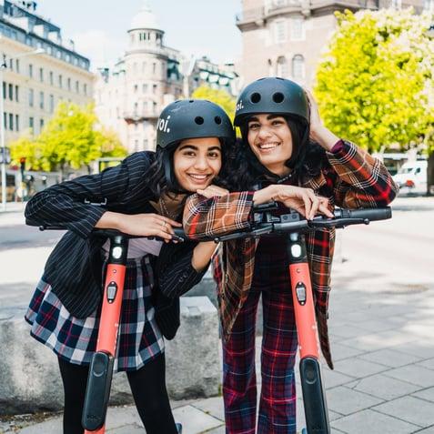 Two women on e-scooters, wearing helmets