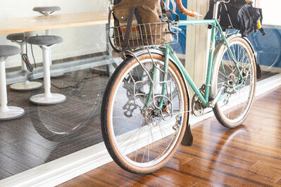 bicycle leaning against a glass wall inside an office